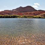 Bottling the Colorado River. Mountain of red sandstone and thin water ripples