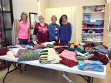 Needlecrafters Cindy Jensen, Judy Ault, Kathy Muhlbeier and Carmen Gilkey along with the hand-made lap robes and shawls being gifted to the local nursing home. A special thank you to three other Needlecrafters not in the photo: Lorraine Downes, Arleen White and Carol Johnson.