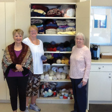 Jan Strycker modeling a shawl, along with Judy Ault and Phyllis Flail around the yarn cabinet at Studio 2 in CAC.