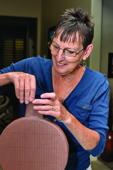 Robson resident Barb Beavers puts the finishing touches on one of her hand-built pottery pieces.