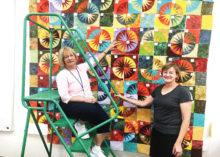 Jodie Spillar and Deb Ellis putting the 2020 raffle quilt together.