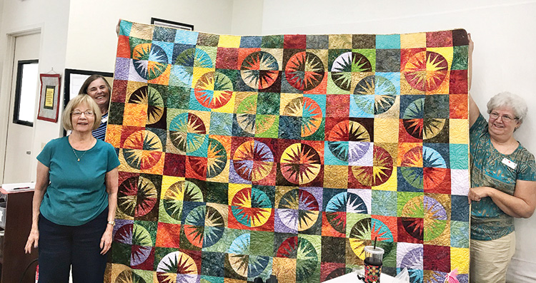 The 2020 Raffle Quilt is finished, and tickets are available for sale. Pictured are Jodie Spillar, Joanne Johnson, and Susie Klopp, three members of the committee who made the quilt. Other members included Diane Bohmert, Lou Downey, Deb Ellis, Karn King, Donna Payne, Barbara Renthal, Kathy Riggs, Liz Seaman, Dottie Welsh, and Sharon White.
