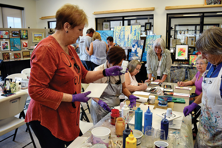 In the foreground, Janet Buckingham assists attendees in the practice of pouring, while in the background, Joanna Bunyea and Sharon Nergaard teach colored pencil technique.