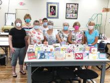 Ladies in the masks (left to right): Pam Dunfee, Sandy Kantrud, Nancy Barnes, Pat Serviess, Janie Toth, Georgia Brosnihan, Diana Sitker, and Debra Forsnight.