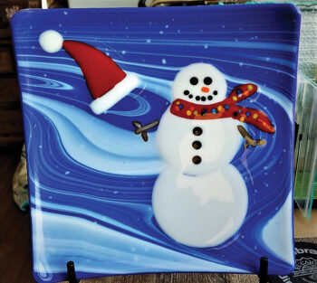 Snowman whose hat is flying off plate by Susan Vaupel