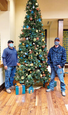 Maintenance team members Kacey and Alex set up and decorated the Christmas tree with the help of Marco (not shown).