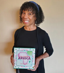 Suzanne Bowman Williams with her book It All Started in Africa