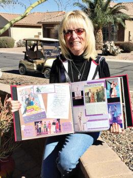 Linda Gayer holding scrapbook