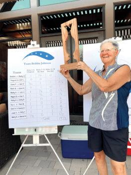 Team captain Bobbie Johnson proudly holds the winner's trophy for the Blue Team.