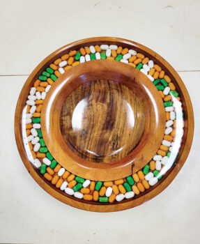 This is a 9-inch bowl made of walnut and mahogany and has tic-tacs inlaid in epoxy.