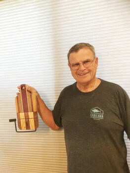 Bill Steursel holding his unique cheese cutting board with wire cutter.